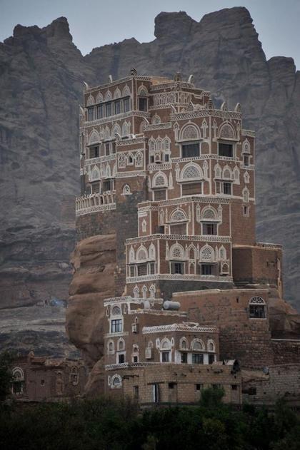 The Dar al-Hajar (Rock Palace) perched atop a rock pinnacle at the Wadi Dhahr Valley in Yemen