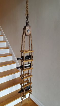 Handmade from my own design, this unique piece incorporates a vintage wood 6 pulley, reclaimed hardwood flooring planks, and 5/8 natural manila rope. Holds 6 standard size bottles and hangs easily from screw eye (included) in ceiling joist or from wall fixture. Includes 8 hand spliced rope for hanging. Measures 65 long from pulley hook to bottom.
