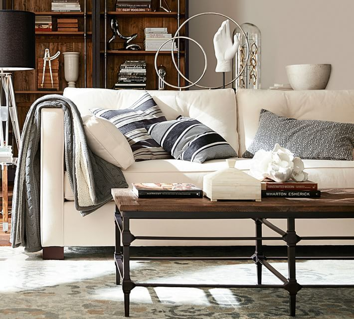 a beautiful cleanlined sofa sets the stage to layer graphic pillows in muted tones letting the collection of found objects take center stage