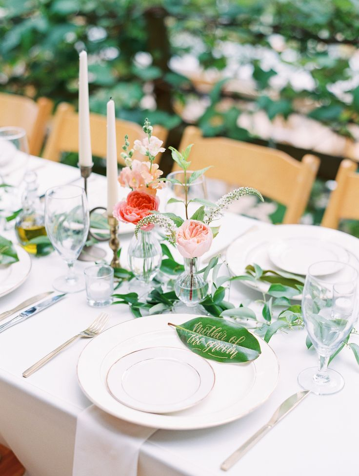 Swoon Floral Design went delicate and romantic for these cluster centerpieces. Clear bud vases housed garden roses and stock while trailing vines of greenery trailed across the tables.