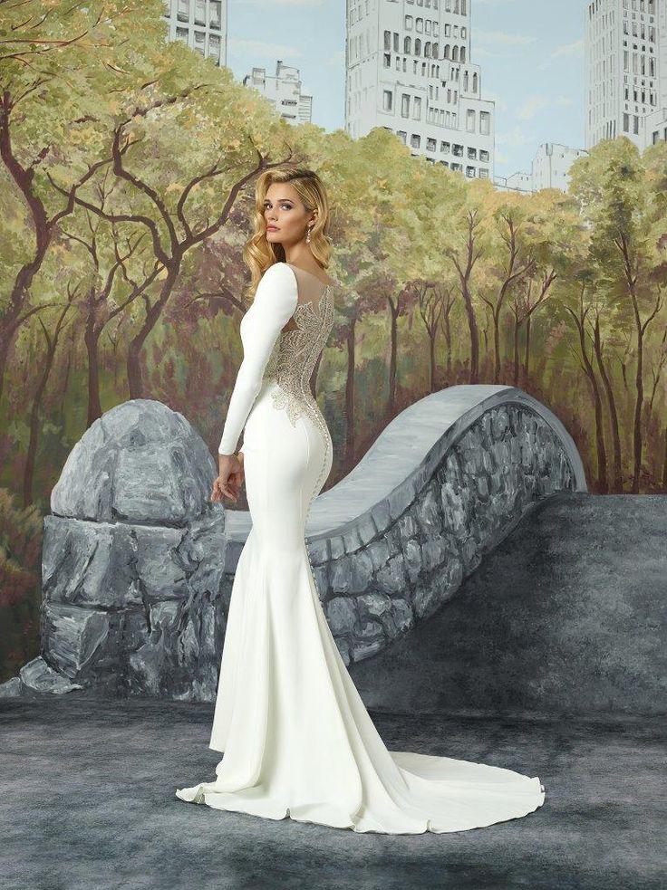 Den mest fantastiske brudekjole i havfrue-snit. Bemærk den dybe ryg som er strøet med sten og perler. Brudekjolen har lange ærmer, der sidder smalt til, og kjolen fremhæver alt feminint ved figuren i sit smukke, bløde snit.