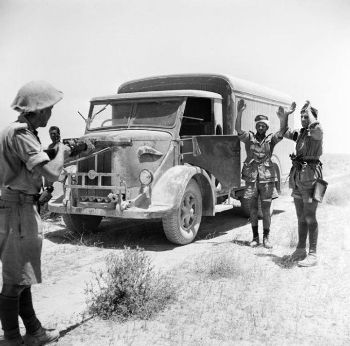 A British infantryman takes the surrender of the crew of an enemy supply truck in the Western Desert 2 June 1942.