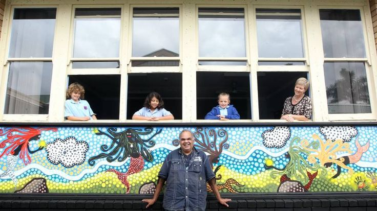 Aboriginal artist Uncle Kevin Butler in front of the new indigenous mural at Woonona Public School with pupils Jaaron Faux Collard, Olivia Jacobs and Chloe Windeyer, and teacher Lauren Borst.