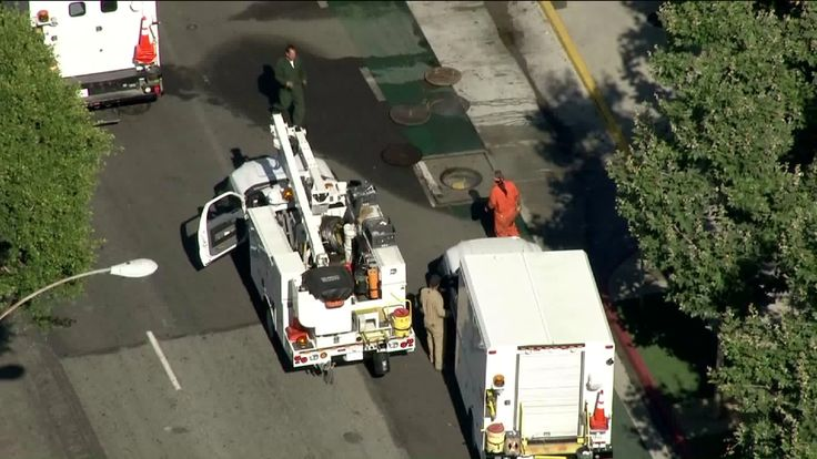Utility crews were working in Long Beach to repair an issue that resulted in several manhole covers blowing into air near the downtown area. (Credit: KTLA)