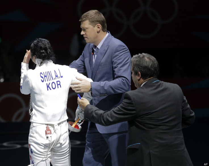 Alright, Time To Go.  Officials lead South Korea's Shin A-lam off the floor after an appeal to an officials decision in a women's individual epee fencing semifinals match against Germany's Britta Heidemann at the 2012 Summer Olympics, Monday, July 30, 2012, in London. (AP Photo/Dmitry Lovetsky)