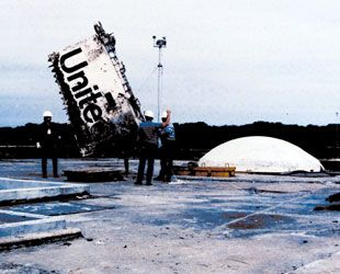 """A crane lifts part of the Space Shuttle """"Challenger"""" recovered from the ocean after it's fatal mission Jan 28, 1986. It exploded 65 seconds into launch. Frozen O-rings failed, allowing gas to blow the fuel tanks off. They were made by Morton Thiokol who accepted no liability though they knew the part would fail. Inept NASA officials went along with the launch to please Pres. Reagan. In a political move Pres. Bush cynically presented the dead crew with the Medal of Honor before the 2004…"""