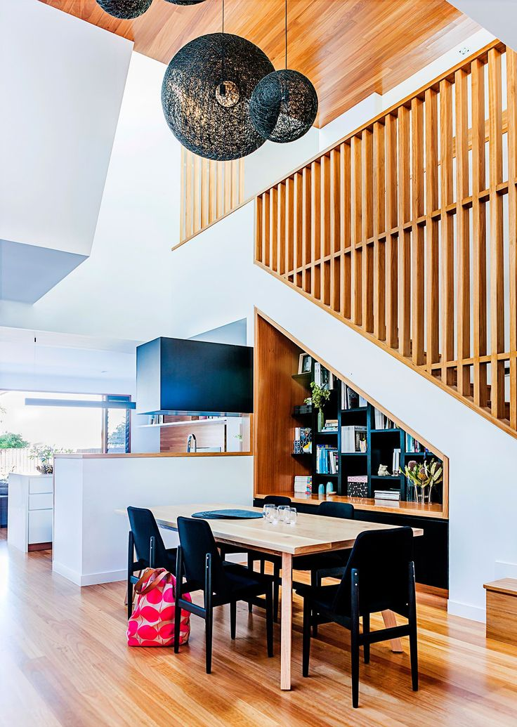 """At the heart of the house is a dramatic double-height void. The dining chairs were a reconditioned roadside find. """"There's lots of storage throughout the house, with a library under the staircase, custom-built joinery in both of the living areas and study desks both upstairs and down,"""" says architect Shaun Lockyer. Custom **table** by [Green Cathedral](http://greencathedral.com.au/