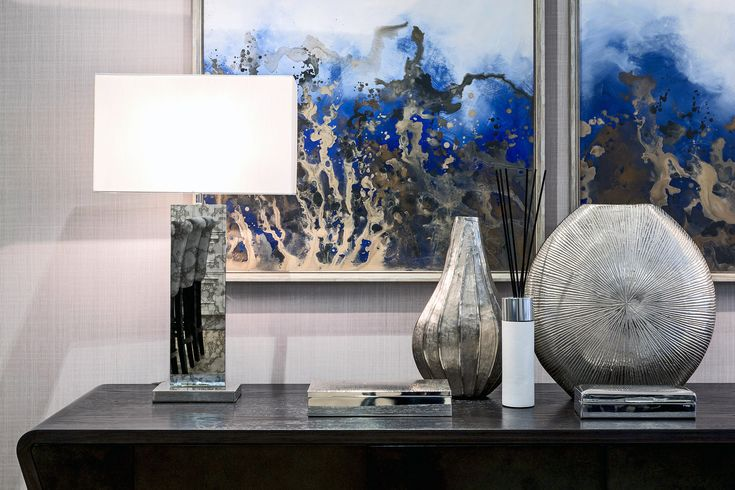 Echoing the metallic brushstrokes of the abstract prints behind, these contemporary Laceby table lamps by RV Astley are striking in their smudge mirror nickel effect, beautifully accompanied by the metallic accessories beside.