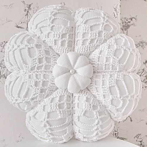 Lace-covered pincushion....maybe a good use for some small crocheted medallions that are laying around.