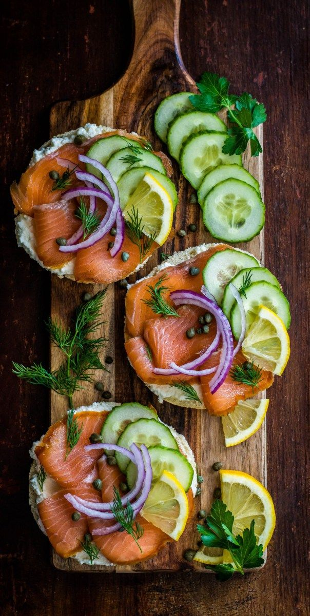 Bagels smeared with cream cheese, then piled high with lox, capers, onions and…
