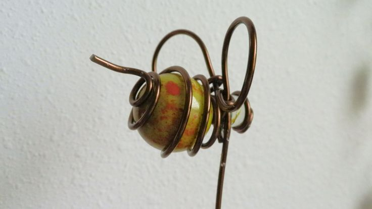 Bee, wire wrapped marble, flower stake. widow charm, sun catcher. I made this garden art.