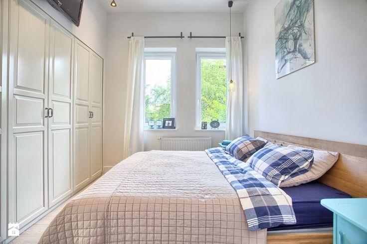 Mała sypialnia z dużym łóżkiem i białą szafą wnękową na całą szerokość ściany