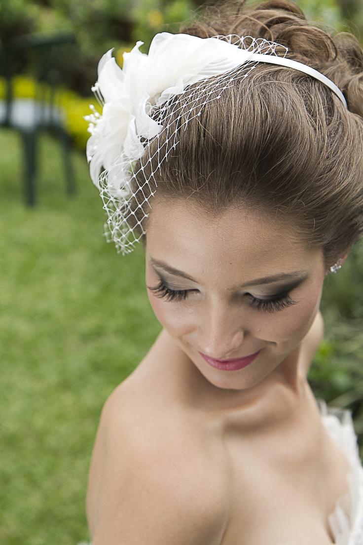 Tiara Gisele para noivas com flor em cetim e organza, com detalhes de pistilos de vidrilho e arrematada por um delicado voilette, na cor off-white, R$ 310,00