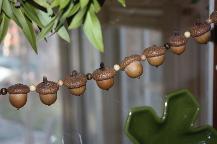 OR drill through the acorn from top to bottom and use a red wooden bead in between each acorn.