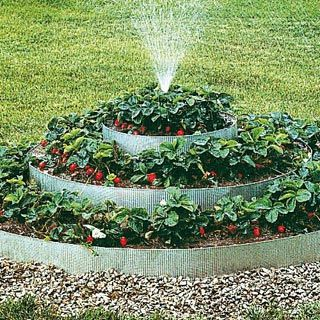 pyramidal strawberry bed with sprinkler good idea for the front yard especially when sprinkler is