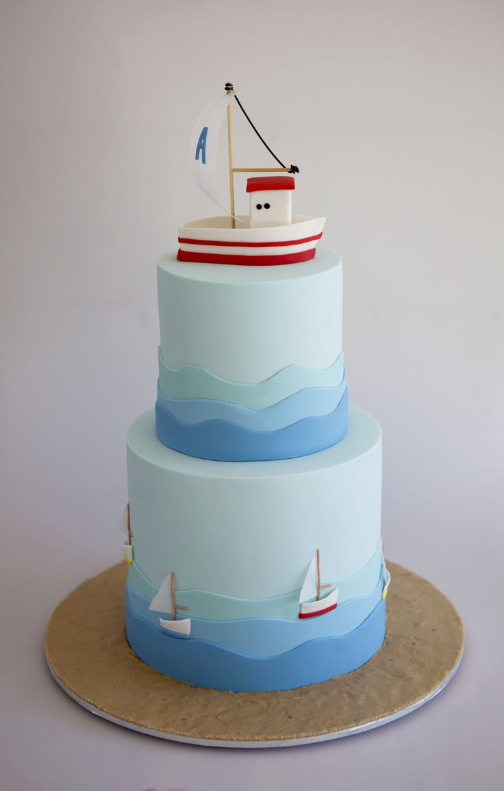 https://flic.kr/p/d4Vyad | A christening cake for Alexandros | A towering cake created for a christening. The topper is modelled on the favours given to guests. Waves of blue fondant lap around both tiers, little sail boats with rice paper sails encircle the bottom tier. Sugar sand features on the board.