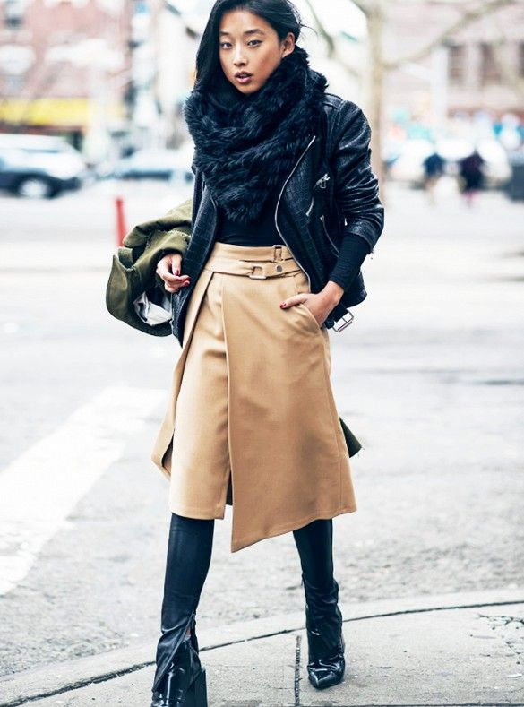 Margaret Zhang wears leather pants with an asymmetrical skirt, leather jacket, and ankle boots: