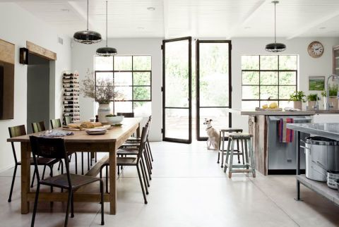 In the dining room of this California home, steel chairs from ABC Home contrast with a massive century-old mahogany dining table, now pickled a paler hue. The homeowner bought the lamps—repurposed chicken feeders—at Cisco Home, and the metal wine rack at the Rose Bowl Flea Market. The walls are painted Plaster of Paris by Sydney Harbour.