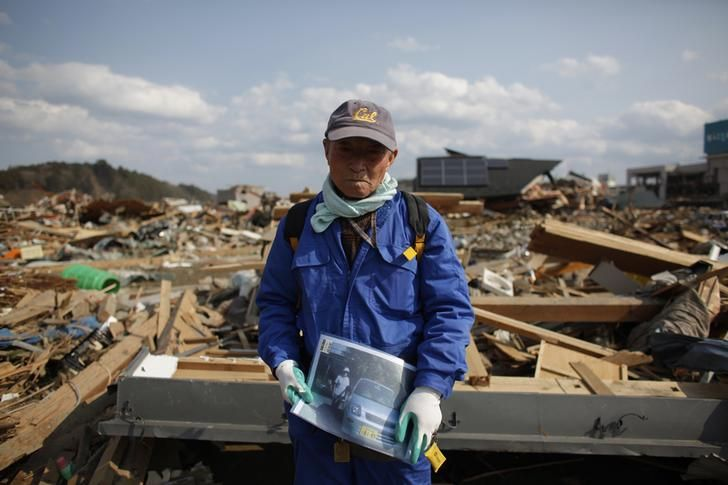Shigemasa Kanno, 74, holds a photograph of his missing 68-year-old wife Sueko Kanno, at the debris of his destroyed house in Rikuzentakata, Iwate prefecture, March 19, 2011. He has been searching for his wife amid the debris. The area was devastated by a magnitude 9.0 earthquake and tsunami on March 11. REUTERS/Aly Song