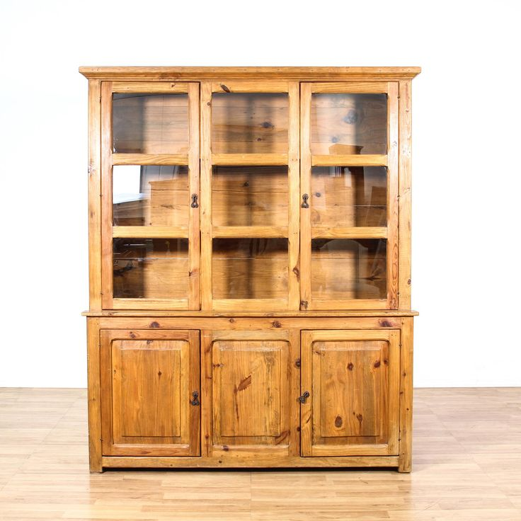 This cabinet is featured in a solid pine wood with a glossy finish. This country chic style display hutch has 2 glass panel doors, 3 shelves, 2 bottom side cabinets with interior shelving, and carved trim. Perfect for showing off curios or fine china! #countryfarmhouse #storage #bookcase&shelving #sandiegovintage #vintagefurniture