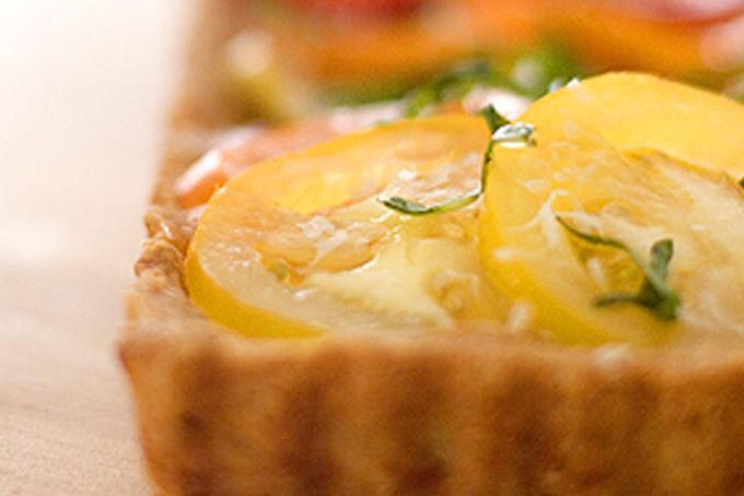 Heirloom Tomato Tart in a Parmesan Crust    This recipe will make one 9 or 10-inch tart OR five 4 1/2-inch tarts.        6 perfect, colorful, medium-sized heirloom tomatoes - washed and sliced 1/6-inch thick        1 t. fine-grain sea salt      1/2 cup unbleached all-purpose flour      1/2 cup whole wheat flour        1/2 cup unsalted organic butter, well chilled + cut into 1/4-inch cubes        4-ounce chunk of good fresh Parmesan, microplane-grated (you should end up with about 2 cups…