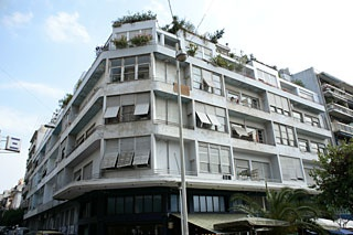 Mple polukatoikia (literally Blue apartment building), Araxovis str, Eksarheia    Designed by Kiriakos Panagiotakos. It owes its name to its original color. Considered a landmark of Greek modern architecture.