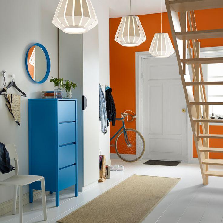 Ingresso con cassettiera blu con 4 cassetti, specchio blu, guardaroba bianco e lampade a sospensione arancioni.