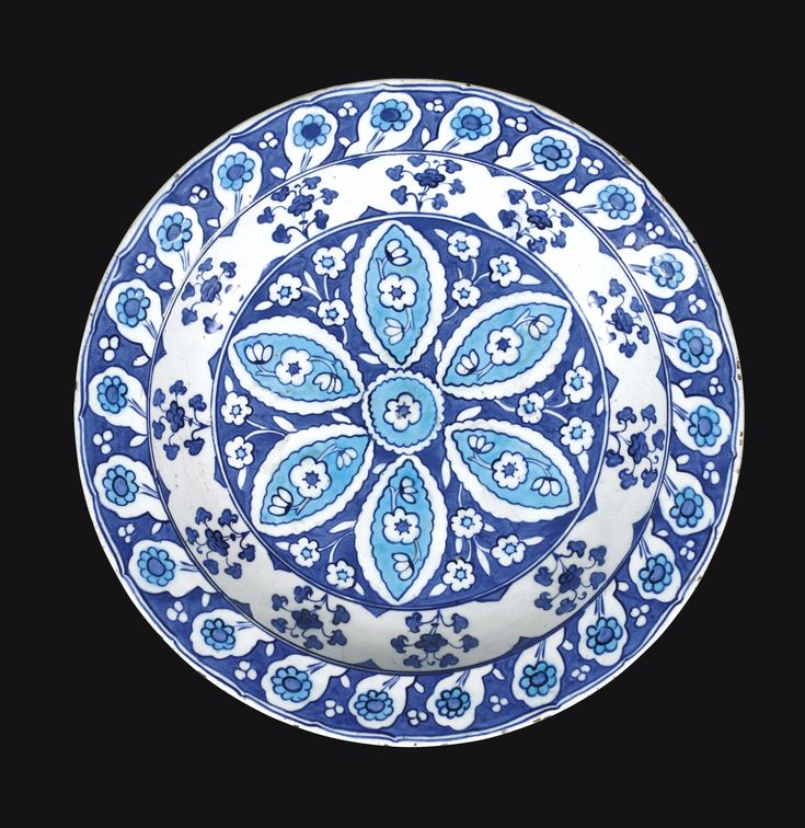 A rare blue and white Iznik dish, Turkey, circa 1535-40 -  Of rounded form with everted rim, the fritware body painted in blue and turquoise on a white ground with a central stylised rosette decorated with floral motifs, bordered by foliate stems, the rim with cintamani motifs between flowers, the exterior with a scrolling foliate design 37.8cm. diam.