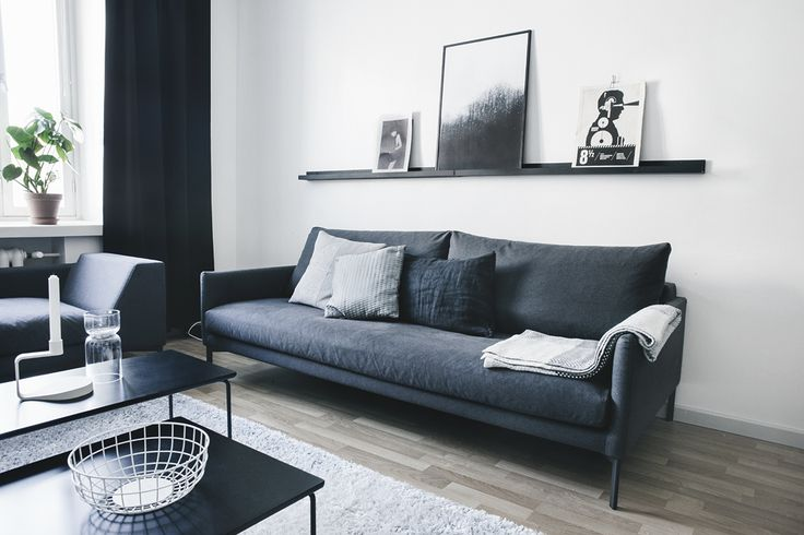 Living room with wood floors, gray rug, black coffee table, dark grey couch, white walls, black shelf with black and white artwork, black curtains, and plants