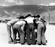 Boys playing baseball in a huddle.