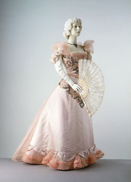 1897 Evening dress of pink satin, consisting of matching bodice and skirt, trimmed with machine embroidered lace motifs, pastes, artificial pink roses and ruches of gathered tulle. [Bodice] The bodice has a low, square neckline, tulle and flower shoulder straps and a floral design applied to the front. The panel at the centre back is veiled in gathered tulle and a ruche of the same tulle trims the slightly pointed waist.