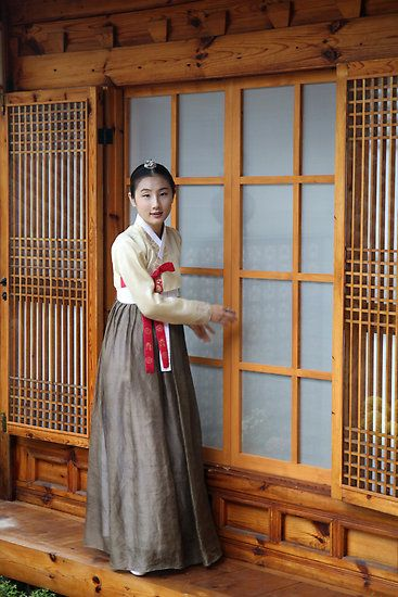 A woman wearing a traditional Hanbok costume at the screen door of a Hanok traditional house.  Seoul, South Korea