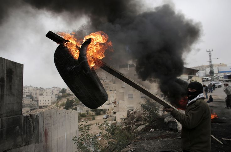 Palestinian protesters burn tyres in front of Israel's barrier that separates the West Bank town of Abu Dis from Jerusalem. ■ Photo: Ahmad Gharabli (Getty Images)
