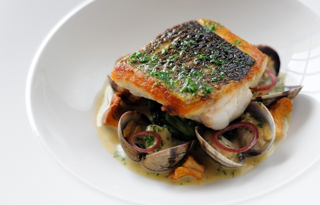 Pan fried sea bass, butter spinach, clams, poached cod cheeks and fish sauce by Simon Hulstone