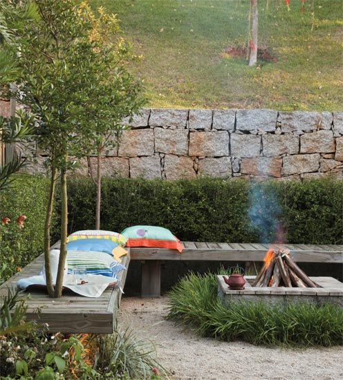 Jardim de estar em torno da fogueira -  notar banco de madeira em L com abertura para arvores Revista Casa e Construcao