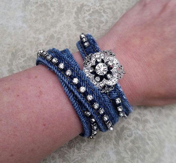 Bracelet en Jean, jeans recyclés, récupérés bijoux, bracelet strass Ce bracelet en Jean a été créé à l'aide de la manchette de jeans. C'est un lavage en denim bleu foncé. Des chaînes de strass ont été soigneusement cousu sur le bracelet à la main. Les points de suture ont été cousus de manière qu'ils ne sont pas vus sur la face arrière du bracelet. Cela donne le bracelet à un fihished, aspect professionnel. Une broche en strass joli a été cousue au centre du bracelet. La broche est 1 1/3...