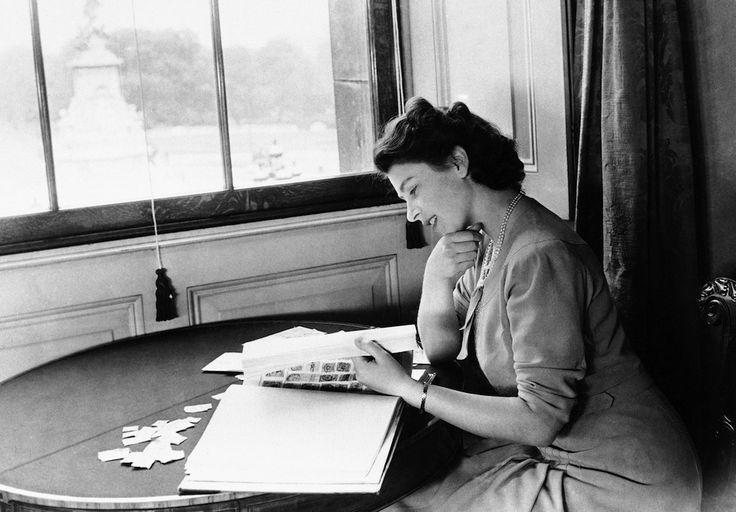 L'allora principessa Elisabetta di Inghilterra, mentre sfoglia la sua collezione di francobolli a Buckingham Palace, Londra, l'11 dicembre 1946