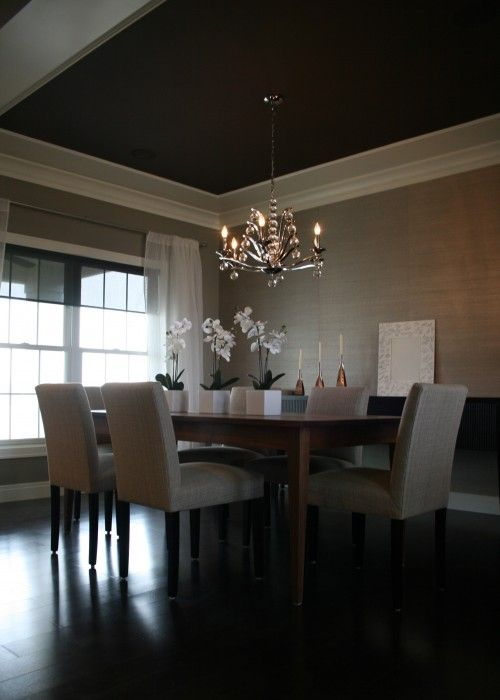Chic dining room design with gray grasscloth wallpaper, white sheers, walnut dining table, gray linen parsons dining chairs, orchids and chocolate brown painted tray ceiling