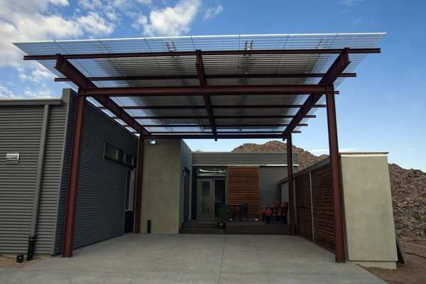 On one side of the house, a carport in front is topped with solar panels. A small deck is tucked by a door to the kitchen. Mechanical systems are hidden behind more cedar-slat panels on the right.