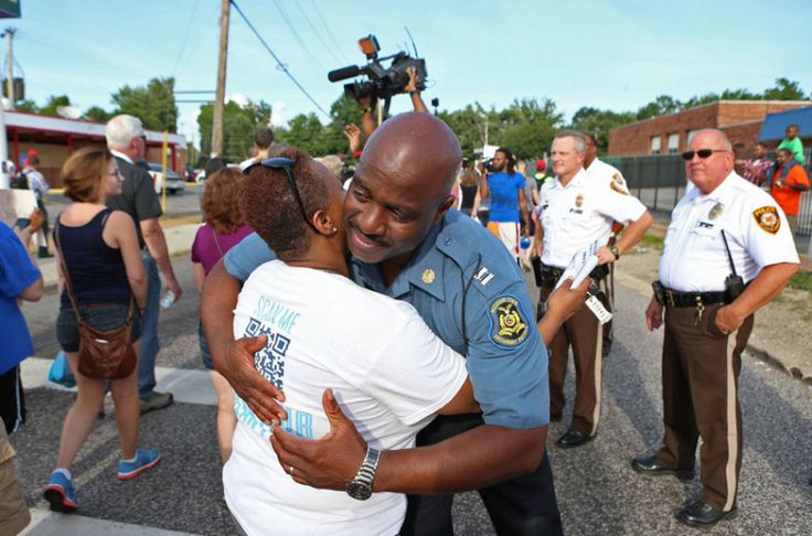 Capt. Ronald Johnson of the Missouri Highway Patrol hugs Angela Whitman, of Berkeley, Mo., on West Florissant Avenue in Ferguson, Mo. Whitman was marching with St. Louis Metropolitan Clergy Coalition. The Missouri Highway Patrol seized control of the St. Louis suburb, stripping local police of their law-enforcement authority after four days of clashes between officers in riot gear and furious crowds protesting the death of an unarmed black teen shot by an officer