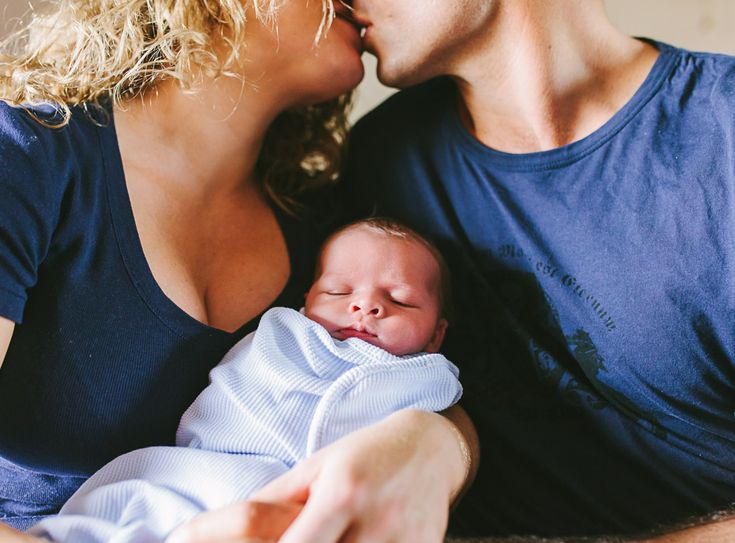 parents kissing over baby