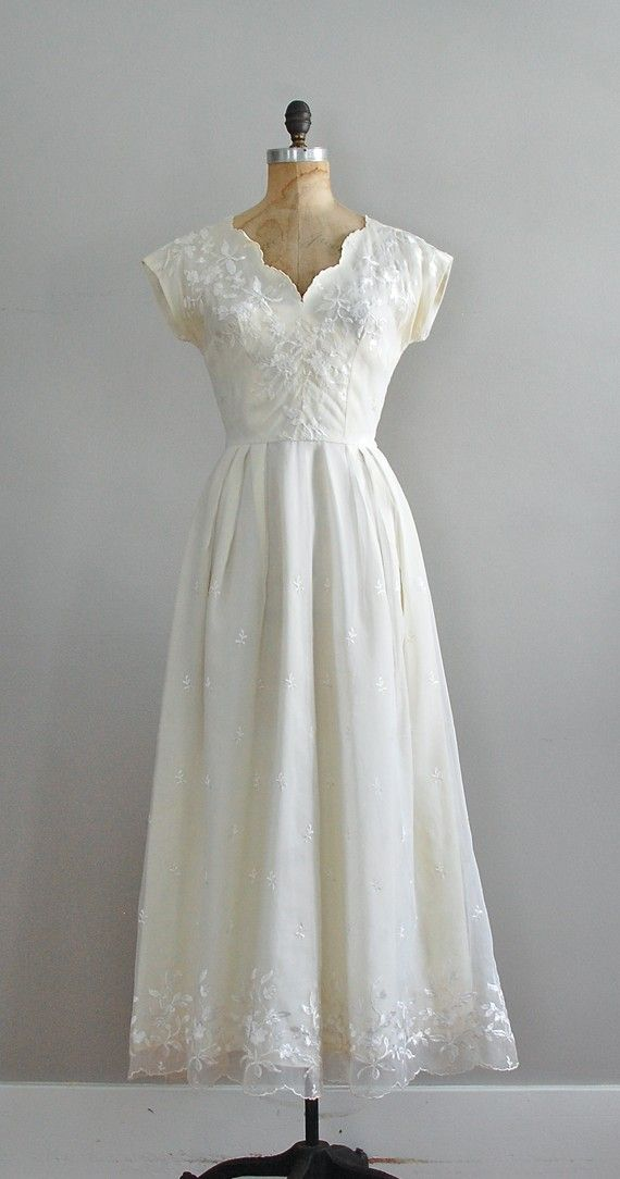 My mother's wedding dress was much like this, except hers was tea length.  I wore it for my going away dress at my own wedding.  Beautiful scalloped neckline and embroidery!