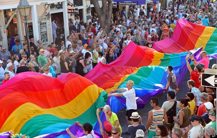 In this photo released by the Florida Keys News Bureau, revelers carry a 100-foot-long rainbow flag, a symbol of gay pride, down Duval Street in Key West, Fla., Sunday, June 10, 201. (AP Photo/Florida Keys News Bureau, Carol Tedesco)