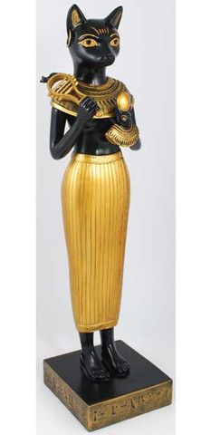 "Shown here in her human form is the cat-headed Egyptian goddess Bastet. With the lithe body of a woman, she bears the symbols of her office as a protector and goddess of Egypt, as well as the gold jewelry of royalty.   Standing approximately 12"" in height, she is sculpted wonderfully out of cold cast resin and is painted in the traditional colors of ancient Egypt; black and gold. $36.95"