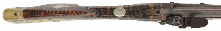 "The brass buttplate is shaped with broad panels that are hand engraved with a checkered pattern.     The front edge of the comb is defined with raised carving. The wrist is fitted with an oval thumbpiece.  The lock panels taper widest at the rear and a panel of raised carving surrounds the flared tang.  The barrel is fitted with a full buckhorn rear sight. dovetailed 11-1/2"" ahead of the breech.  The tall nickel silver blade front sight is dovetailed behind the muzzle."