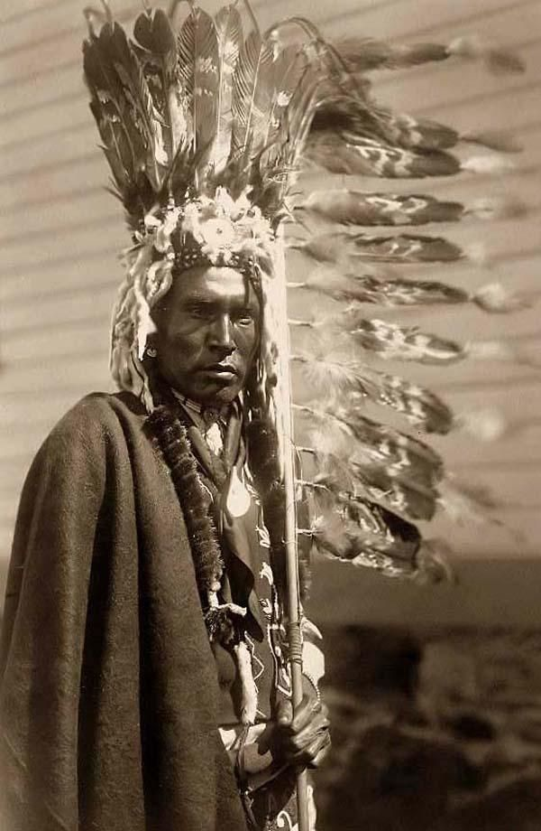 Here for your consideration is an aesthetic picture of a Piegan Warrior dressed in a War-bonnet and holding a Coup-stick. It was created in 1910 by Edward S. Curtis.    The picture presents a Piegan man, half-length portrait, dressed in war bonnet and holding a feathered coup-stick, facing front.    We have created this collection of illustrations primarily to serve as a valuable educational tool. Contact curator@old-picture.com.