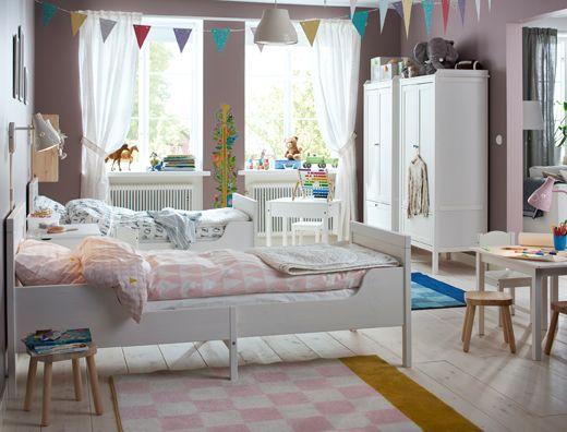 Dvě roztažitelné postele vedle sebe, růžovo bílá ložnice