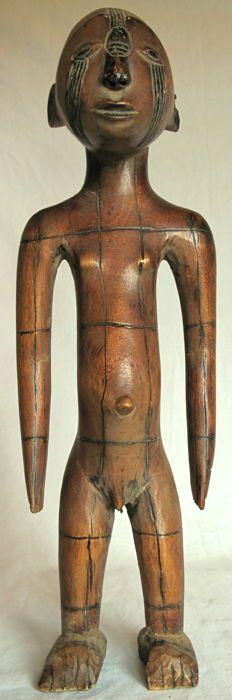 Zeer elegante staande man sculpture - of - N.E. D.R.C.  Een vrijstaande mannelijke figuur met klassieke langwerpige hoofd het kapsel fijn ingesneden met verticale en horizontale groeven. Gezicht littekens tussen de ogen op het voorhoofd en de wangen. Conische hoofd overkoepelende wenkbrauwen amandelvormige ogen korte dunne neus en vooruitstekende half open mond. Grote ronde oren. De lange armen gesneden gratis van het slanke lichaam; de navel uitsteekt. Kleine sex. De benen bijna direct met…