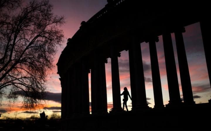 A woman walks among columns at the Retiro park in Madrid, Spain