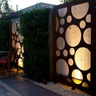 Fences With Flair: Decorative metal panels, allowed to rust naturally, dress a once-plain wooden fence. Lighting behind the panels extends outdoor entertaining into evening and adds drama to the space.